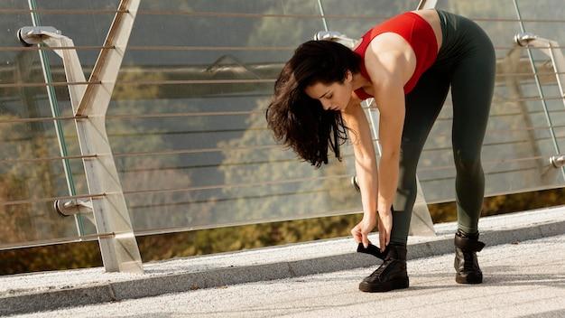 Jeune femme attachant ses lacets de chaussures