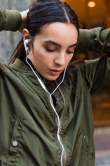 Jeune femme, attacher, elle, cheveux, musique écoute, sur, écouteur