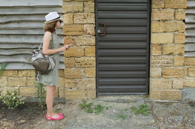 Jeune femme attend devant la maison