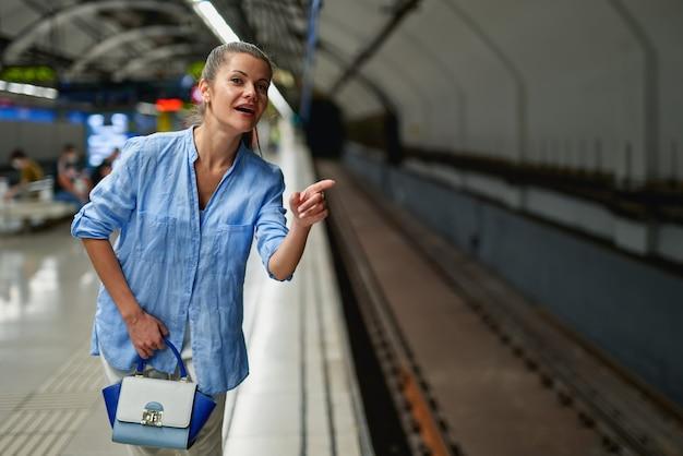 Jeune femme attendant sur le quai d'une gare l'arrivée du train. transport public.