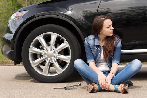Jeune femme en attente d'assistance routière
