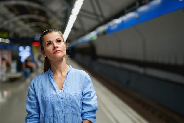Jeune femme en attente sur le quai d'une gare ferroviaire pour l'arrivée du train. transport public.