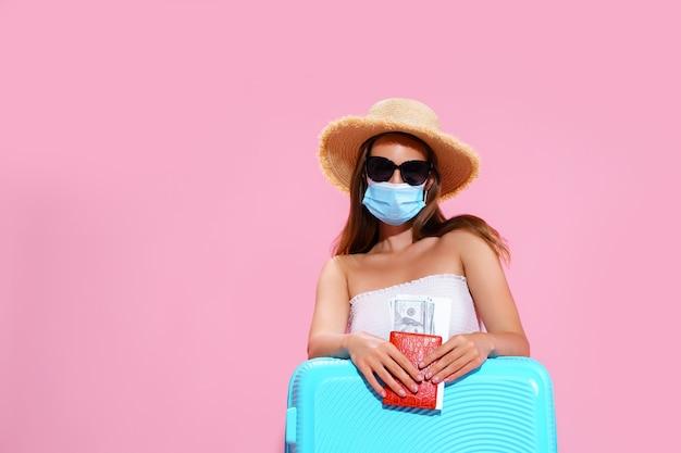 Jeune femme en attente de vol assise sur le sol près de sa valise portant un masque facial pour empêcher le coron...