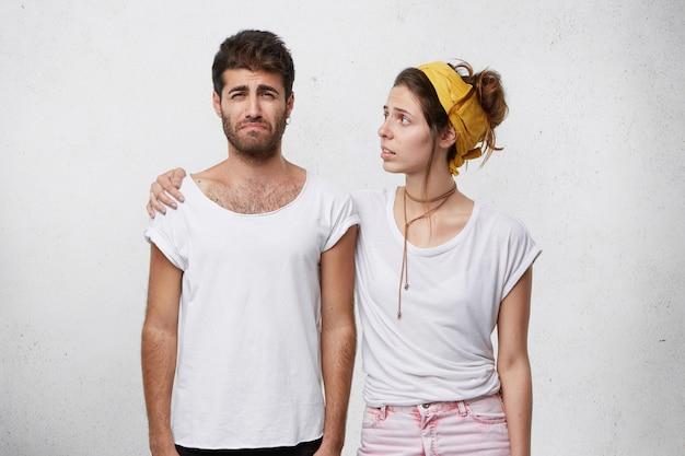 Jeune femme attentionnée et compatissante regardant son petit ami pleurant déprimé malheureux avec une expression inquiète, le réconfortant et le soutenant pendant qu'il est bouleversé à cause de problèmes ou d'échecs au travail