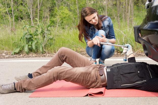 Jeune femme attirante aidant un mécanicien