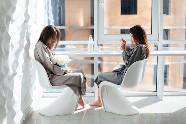 Jeune femme attirante concentrée prenant des photos avec le smartphone de ses soeurs jumelles s'asseyant près de la fenêtre