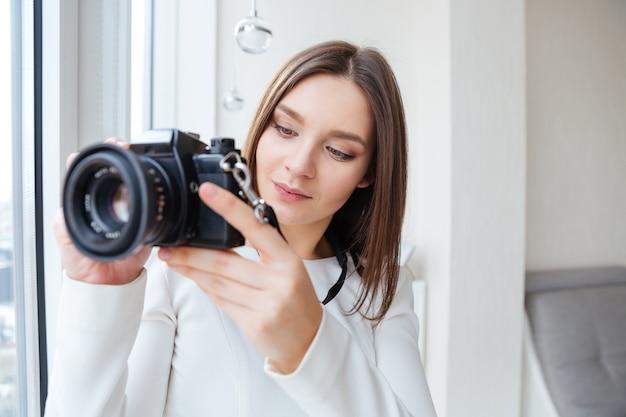 Jeune femme attirante concentrée utilisant l'appareil photo et prenant des photos près de la fenêtre