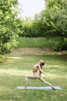 Une jeune femme attirante fait le yoga en parc pendant l'instructeur de yoga d'été