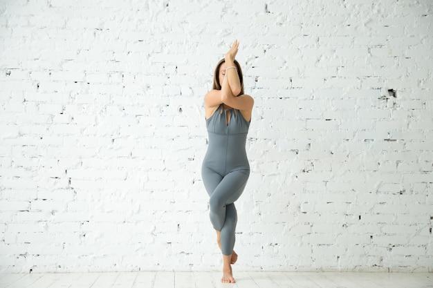 Jeune femme attirante à garudasana pose, studio blanc backgrou