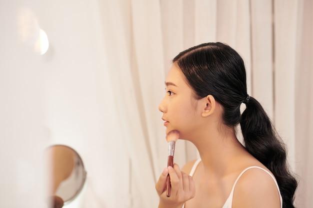 Jeune femme attirante avec le maquillage fait par l'artiste professionnel regardant dans le miroir à l'intérieur