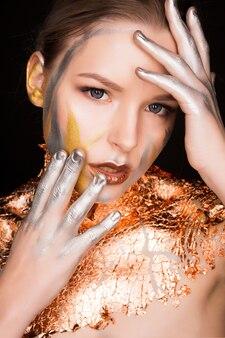 Jeune femme attirante avec le maquillage professionnel et la feuille d'or sur ses épaules et cou