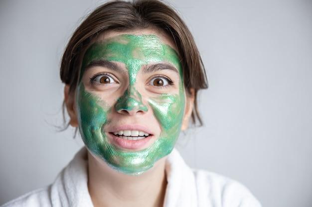 Jeune femme attirante avec un masque cosmétique vert sur son visage et dans une robe blanche