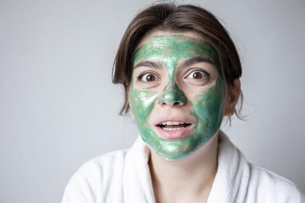 Jeune femme attirante avec un masque cosmétique vert sur son visage