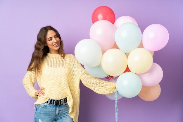 Jeune femme attraper de nombreux ballons sur mur violet