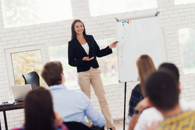 Jeune femme attrayante coacher dirige un séminaire.
