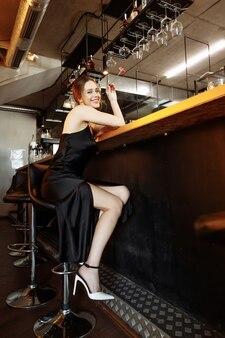 Jeune femme au bar avec une rose photo de haute qualité