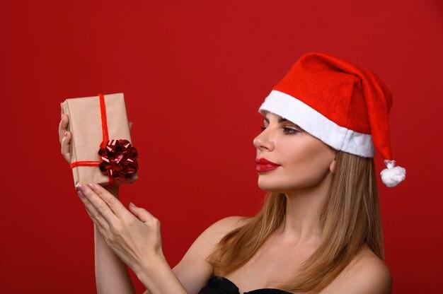 La jeune femme au bonnet de noel envisage un cadeau de noël