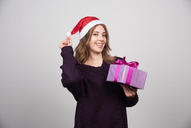Jeune femme au bonnet de noel tenant une boîte-cadeau présente.