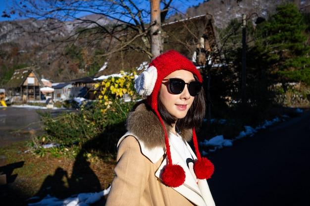 Jeune femme au bonnet rouge avec l'arrière-plan de la ferme en bois du patrimoine.