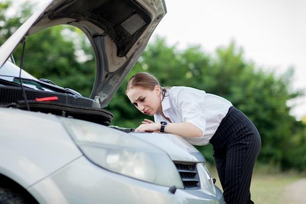Jeune femme au bord de la route après la panne de sa voiture