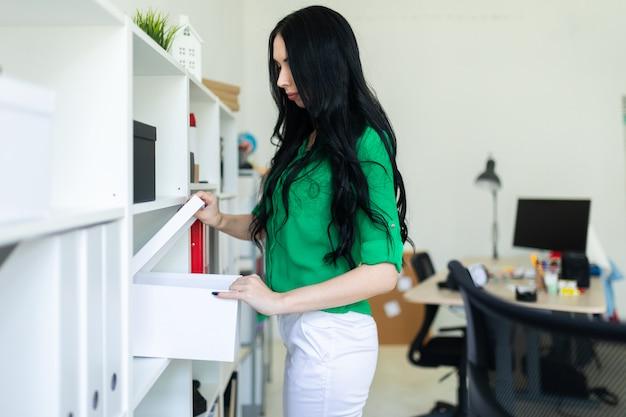 Une jeune femme au bureau sort une boîte blanche.