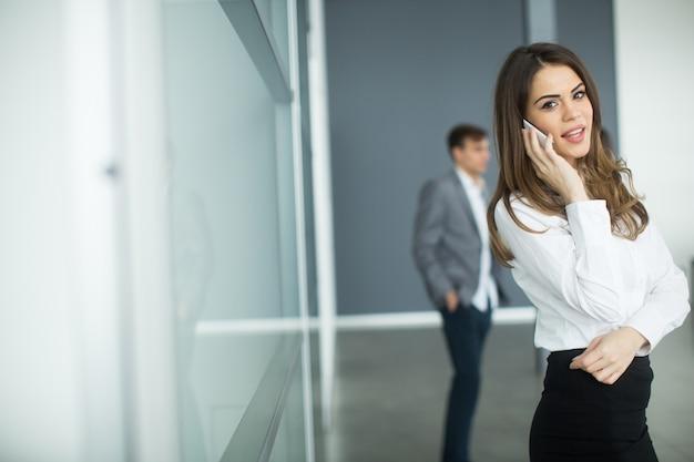 Jeune femme au bureau avec téléphone portable