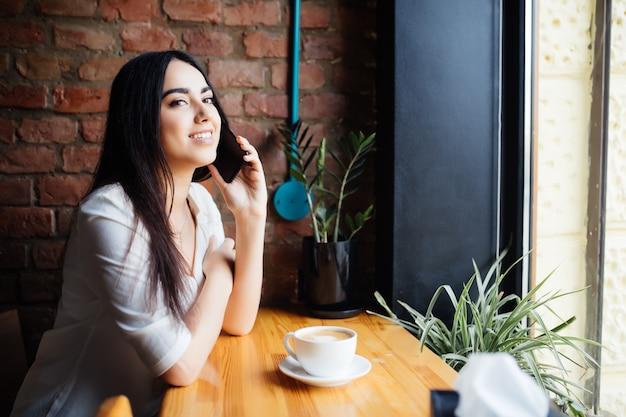 Jeune femme au café, boire du café au café et parler au téléphone mobile à la recherche sur la fenêtre