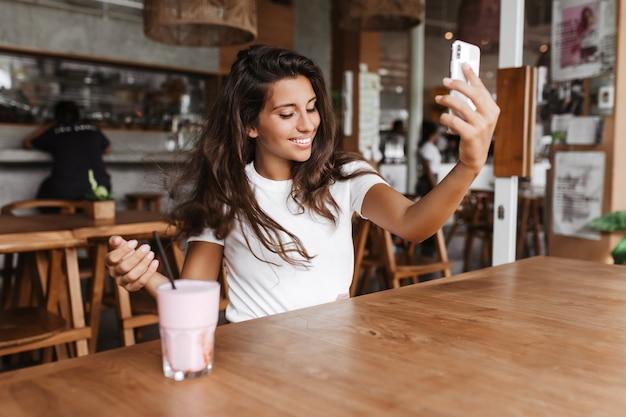 Jeune femme au café avec des meubles en bois fait selfie