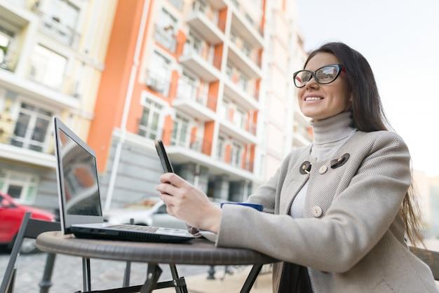 Jeune femme au café avec ordinateur portable