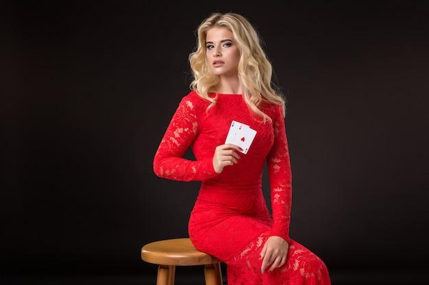 Jeune femme au casino avec des cartes sur fond noir. poker