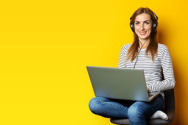 Jeune femme au casque assis sur une chaise et tenant un ordinateur portable sur jaune isolé.
