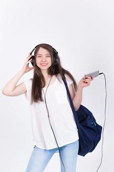 Jeune femme au casque chantant des chansons sur un mur blanc