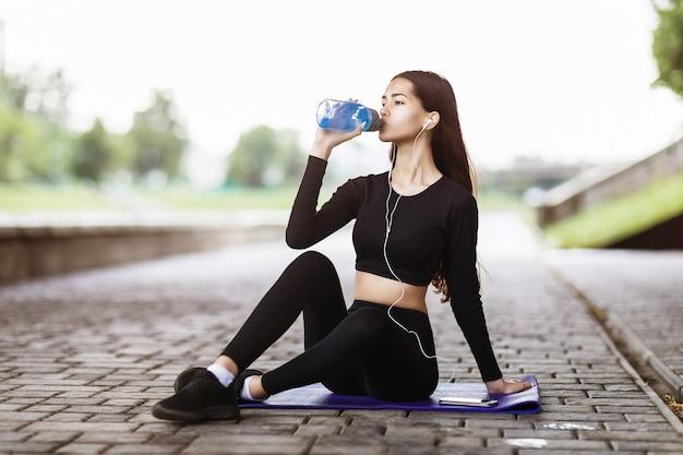 Jeune femme au casque est assise sur un tapis de gymnastique et boit de l'eau après avoir fait du sport dans la rue