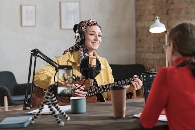 Jeune femme au casque jouant de la guitare et chantant une chanson pendant l'air en studio radio avec radio dj assis en face d'elle
