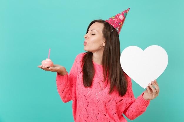 Jeune femme au chapeau d'anniversaire pull rose tricoté avec les yeux fermés soufflant la bougie sur le gâteau tenir coeur blanc avec espace de copie isolé sur fond bleu. concept de mode de vie des gens. maquette de l'espace de copie.