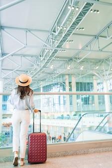 Jeune femme au chapeau avec des bagages à l'aéroport international.