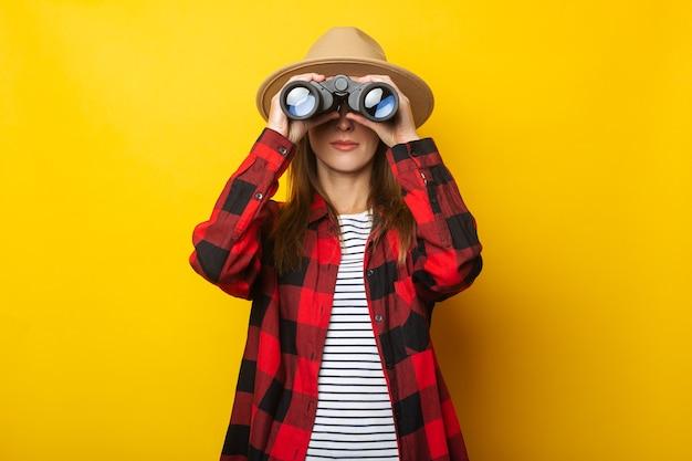 Jeune femme au chapeau et chemise à carreaux regardant à travers des jumelles sur fond jaune.