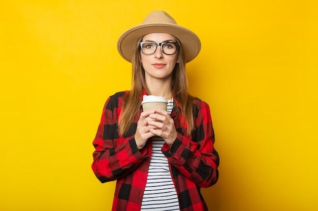 Jeune femme au chapeau et chemise à carreaux tenant une tasse de papier avec du café sur jaune
