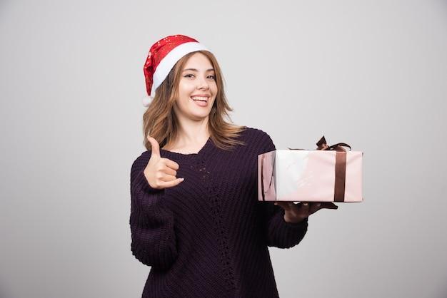 Jeune femme au chapeau du père noël avec un cadeau montrant un pouce vers le haut.