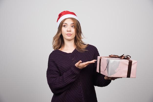 Jeune femme au chapeau du père noël pointant sur un cadeau.