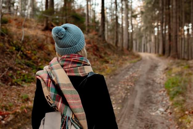 Jeune femme au chapeau et écharpe marchant dans une forêt