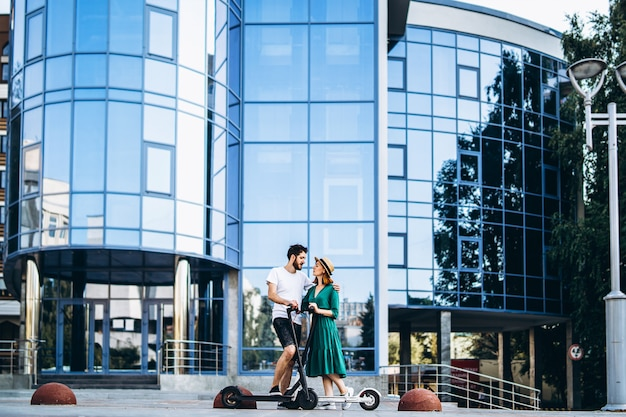 Une jeune femme au chapeau et un homme se parlent et profitent d'une promenade sur des scooters électriques.