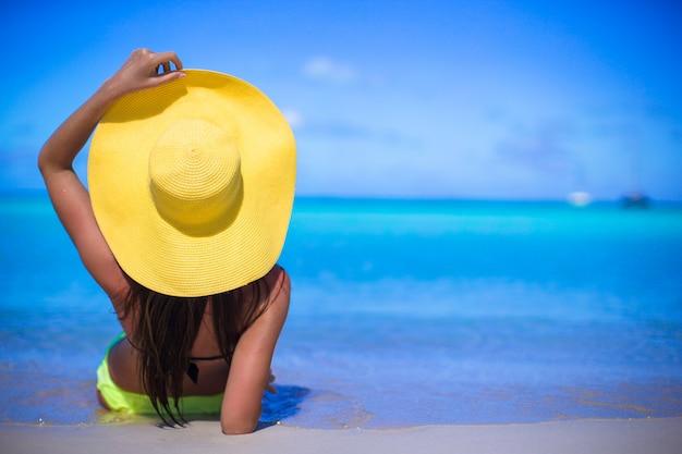 Jeune femme au chapeau jaune pendant les vacances des caraïbes