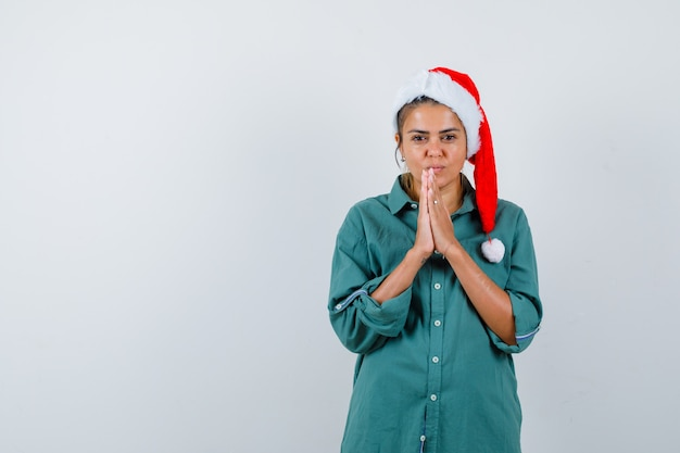 Jeune femme au chapeau de noël, chemise avec les mains en geste de prière et à l'espoir, vue de face.