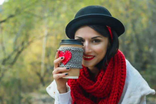 Une jeune femme au chapeau noir boit du café dans une tasse confortable sur la nature. sourire éclatant et bonne humeur