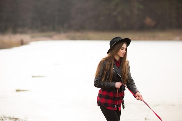 Jeune femme au chapeau noir s'amuser avec son chien