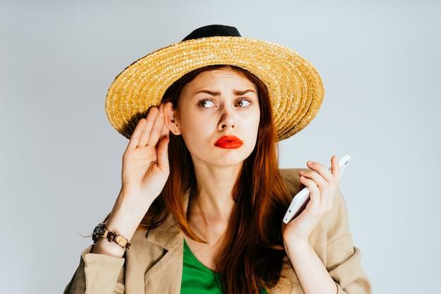 Une jeune femme au chapeau de paille écoute, regarde avec nostalgie vers la gauche. isolé sur un fond gris