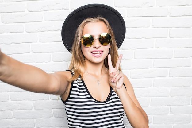 Jeune femme au chapeau de paille et lunettes de soleil prenant selfie smart phone avec geste de paix sur mur de bureau en brique blanche