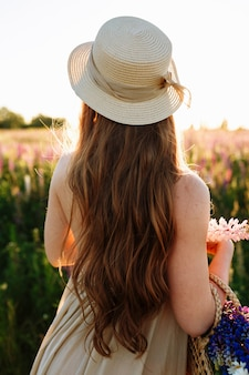 Jeune femme au chapeau de paille et robe avec bouquet de fleurs de lupin