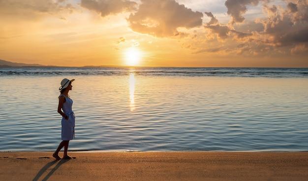 Jeune femme au chapeau de paille et une robe marchant seule sur la plage de sable vide au coucher du soleil au bord de la mer.
